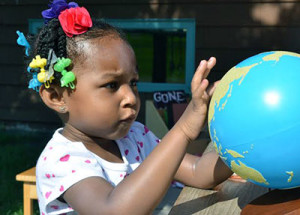 young pupil looks at a globe with curiosity